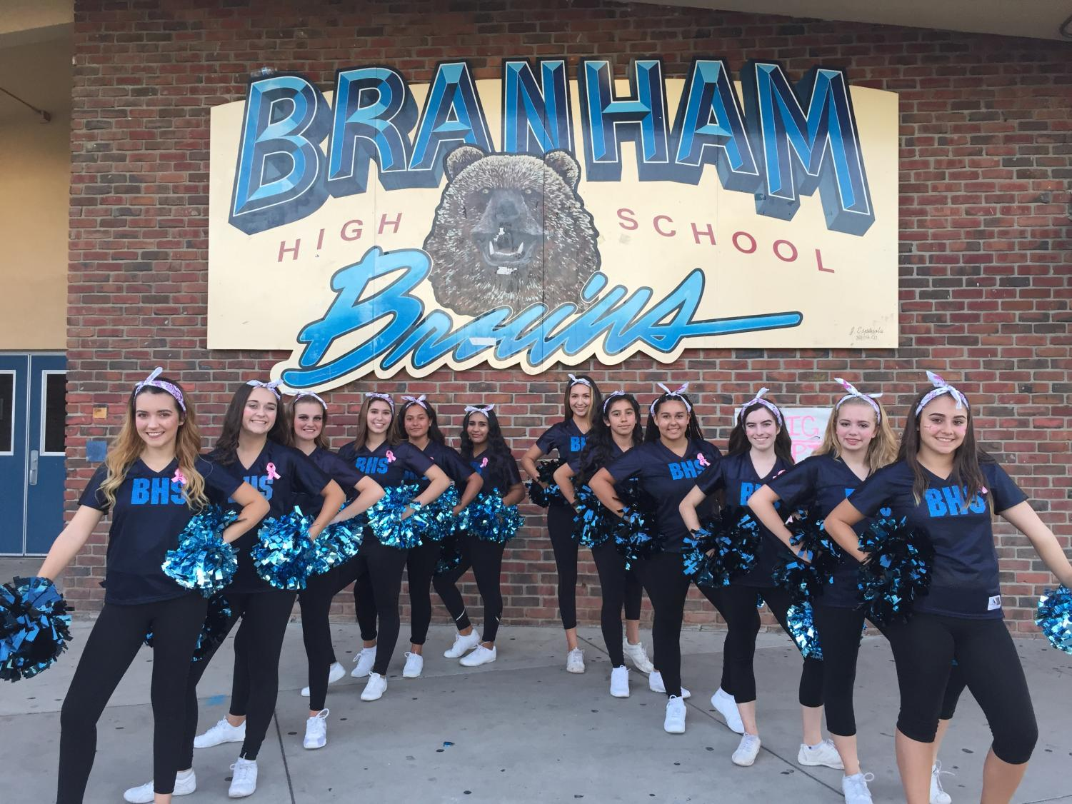 The Branham High School Dance Team poses for a picture in formation outside the large gym during the day.