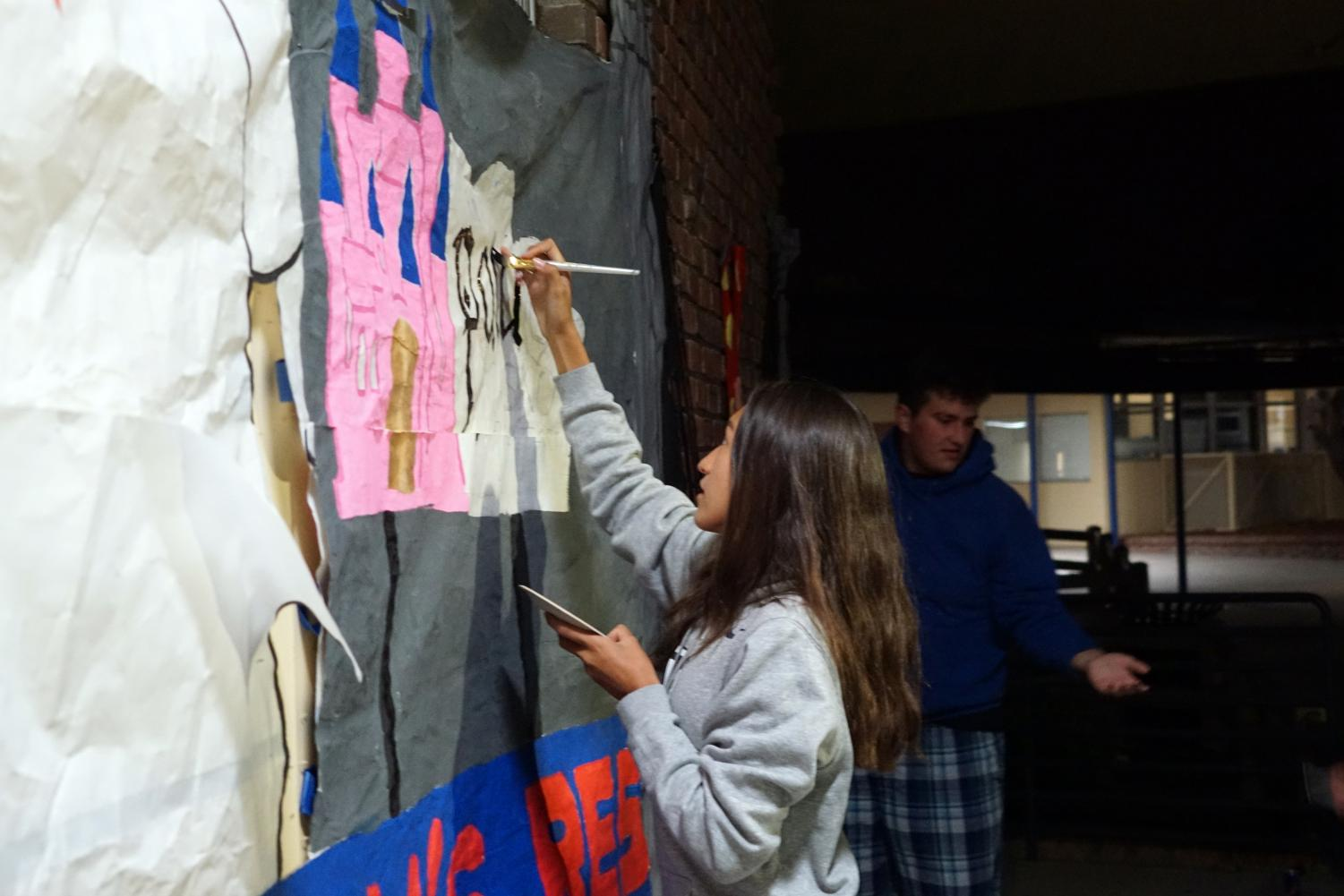Junior Quinn Ruiz and decorating head puts some finishing touches on her homecoming decorations early Monday morning.