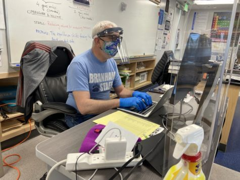 Science teacher Juan Fernandez teaches from his desk surrounded by plexiglass and cleaning supplies. The district and the union both advocated to ensure teacher safety upon retuning in person.